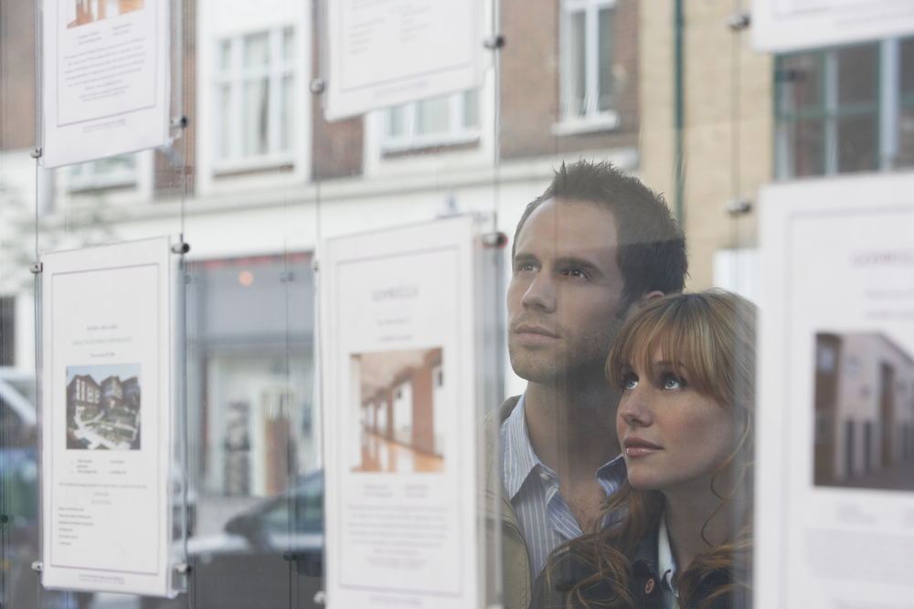 couple looking at house advert in window