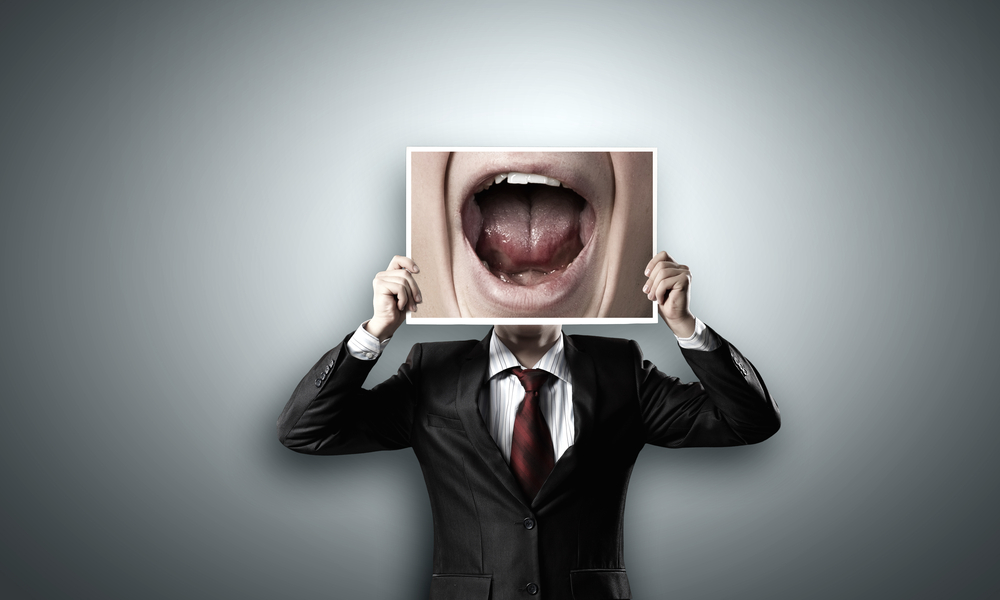 man holding a picture of an open mouth over his face