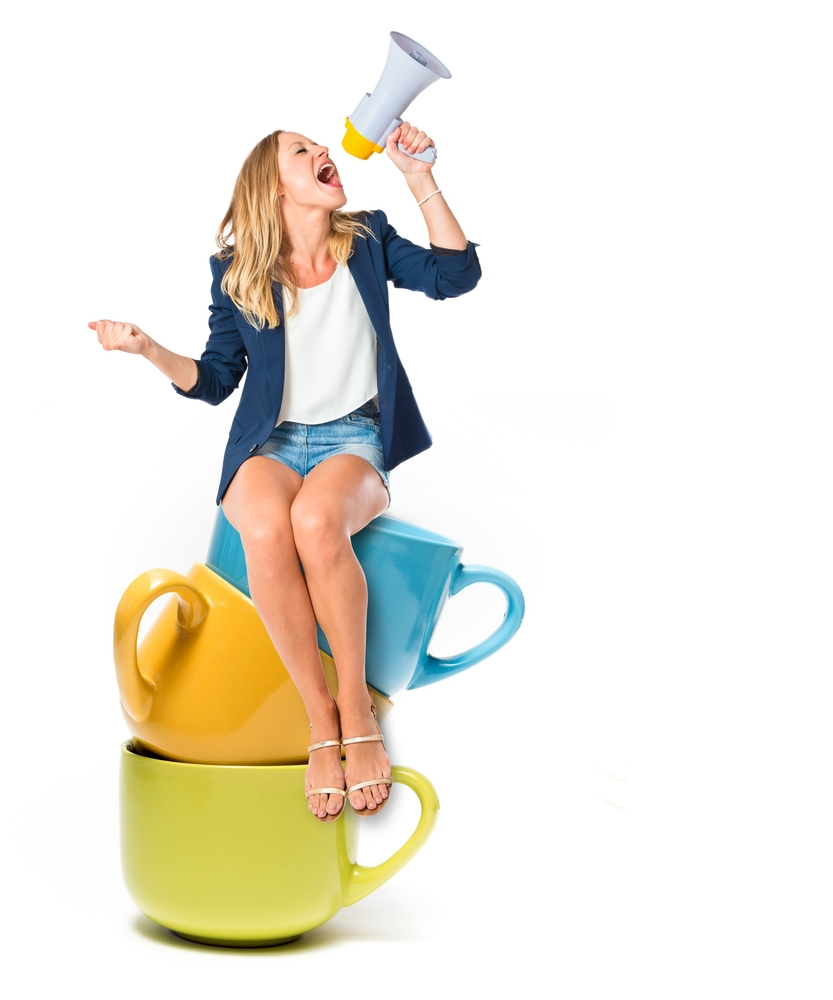 woman sitting on teacups holding a megaphone