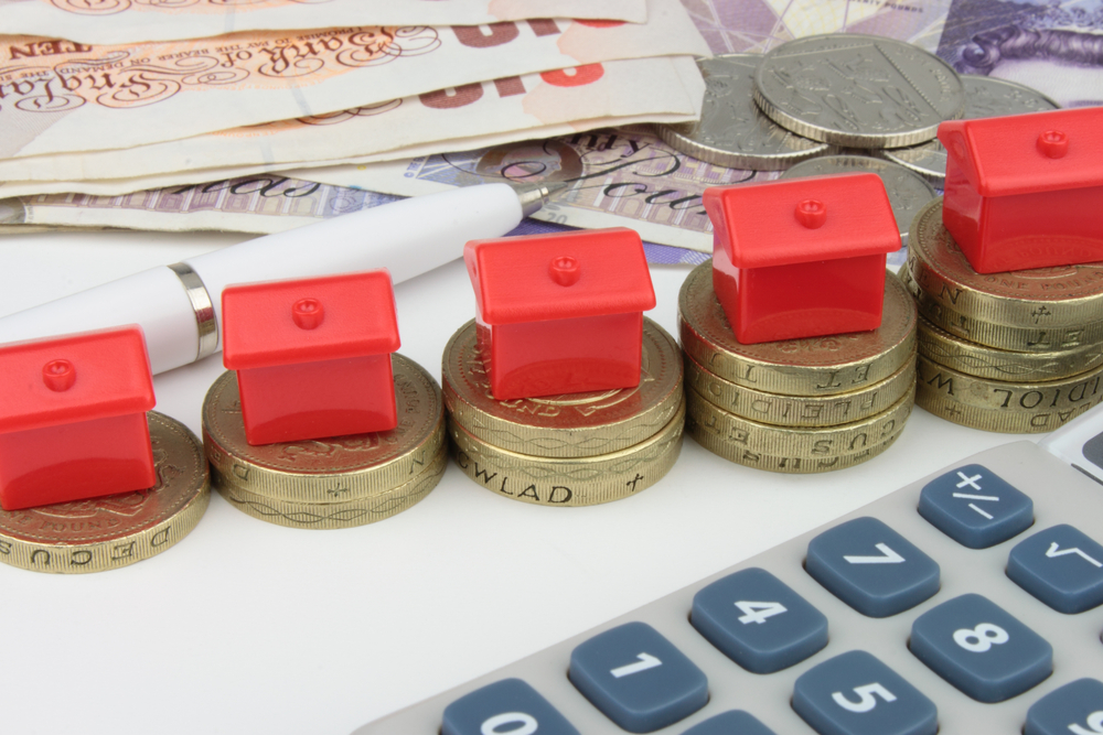 little houses on pound coins next to a calculator