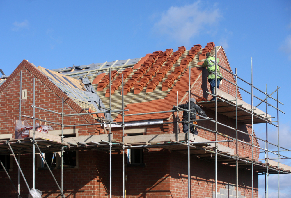 Two builders assemble the roof of a new house