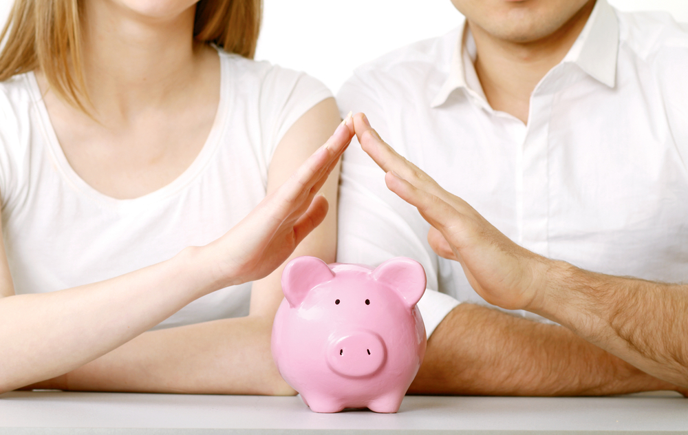Couple with steepled fingers over piggy bank
